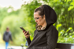 Young woman using smartphone in city park Royalty Free Stock Image