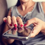 Young woman using a smartphone. Closeup of a young caucasian woman with red nail polish in her fingernails using a smartphone stock photos
