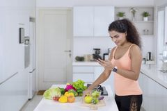 Young woman using a smartphone in the kitchen royalty free stock images