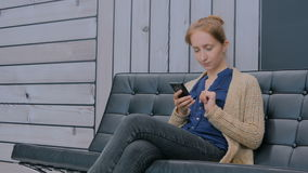 Young woman using smartphone on couch in modern office stock footage