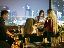 Young woman using a smartphone at a dinner night having no inter. Young women using a smartphone at a dinner night having no interaction with friends addiction stock photography
