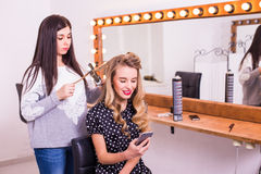 Young woman using smartphone in dressing room Stock Photos