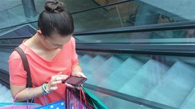 Young woman using smartphone on escalator at the shopping mall and using smart phone. Urban lifestyle, keeping in touch stock video