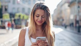 Young woman using smartphone in the European city. Slow Motion. Beautiful girl browsing Internet, searching for maps and. Information, communicating. Travel stock video