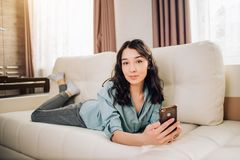 Young woman using smartphone at home. Photo of relaxed caucasian woman watches online story on mobile phone, reads news with amazing information, dressed in stock photography