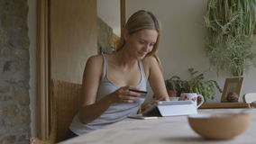 Young woman using a smartphone at home. A young woman is sitting in her home enjoying a cup of tea whilst using social media on her smartphone stock footage