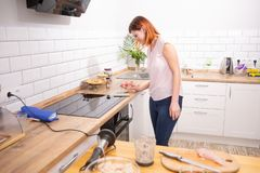 Young woman using smartphone leaning at kitchen in a modern home. woman reading phone message. redhead woman typing a text message stock photography