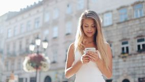 Young woman using smartphone and looking into the camera in the beautiful European city. Slow Motion. Girl browsing. Internet, searching for maps and stock video footage