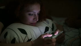 Young woman using smartphone lying on bed at home at night stock video
