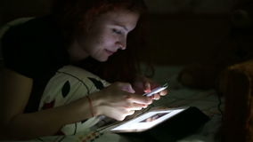 Young woman using smartphone lying on bed at home at night stock footage