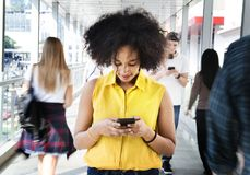 Young woman using a smartphone in the middle of the walking crow. Young women using a smartphone in the middle of the walking crowd royalty free stock photo