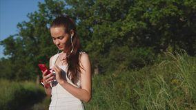 Young woman using smartphone outside at green trees nature background. stock footage