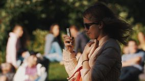Young woman using smartphone outside in park during summer event. Lots of people stock video