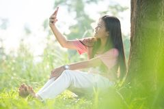 Young woman using a smartphone in the park, Portrait of a beautiful young woman selfie in the park with a smartphone royalty free stock photos