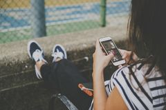 Young woman using a smartphone at the park royalty free stock photography