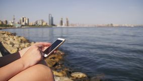 Young Woman using Smartphone Sitting on Embankment near the Sea and Skyscrapers of Megapolis. Young Woman using a Smartphone Sitting on Embankment near the Sea stock footage