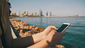 Young Woman using Smartphone Sitting on Embankment near the Sea and Skyscrapers of Megapolis stock footage