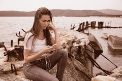 Young woman using smartphone sitting on an old pier Royalty Free Stock Photos