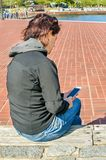 Young Woman Using a Smartphone while Sitting on a Bench on a Sunny Autumn Day Stock Photos