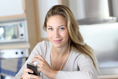 Young woman using smartphone st home kitchen Royalty Free Stock Images