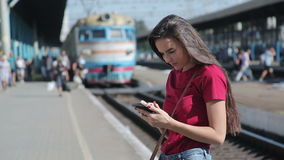 Young woman using smartphone at train station. Girl texting on cellphone while waiting for train stock video footage
