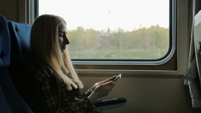 Young woman using smartphone while traveling by train stock video