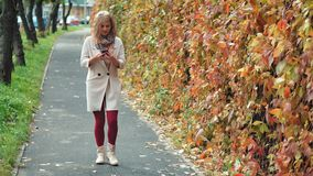 Young woman using smartphone during walk in autumn park stock video