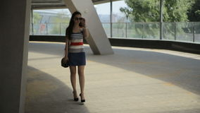 Young woman using smartphone and walking in park in city. HD stock video footage