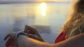 Young woman using smartwatch on beach. Close-up on touchscreen using watch app. Blonde woman searching options in smartwatch on sunset, standing near water stock footage