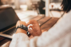 Young woman using smartwatch at a cafe Royalty Free Stock Photos