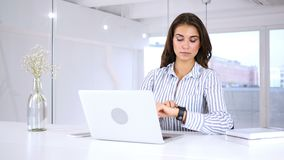 Young woman using smartwatch, sitting in office. 4k, high quality stock footage