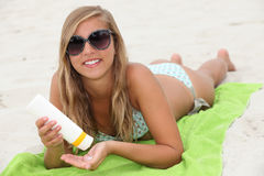 Young woman using sun cream Stock Photos