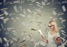 Young woman using a tablet building online business earning money under cash falling down. royalty free stock photo
