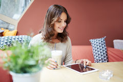 Young woman using tablet at cafe Royalty Free Stock Photography