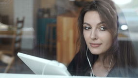 Young woman using tablet in coffee shop with headphone stock video footage