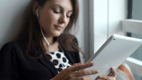 Young woman using tablet in coffee shop with headphone stock footage