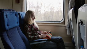 Young woman using tablet in colourful case while traveling by train stock footage
