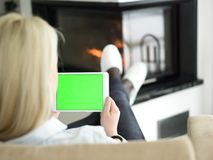 Young woman using tablet computer in front of fireplace Royalty Free Stock Photo