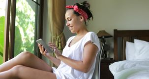 Young Woman Using Tablet Computer Happy Beautiful Girl Chatting Online Over Big Window With Tropical Garden View. View Slow Motion 60 stock footage