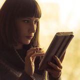 Young Woman Using Tablet Computer near window. Warm color toned image Stock Photos