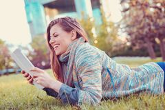 Young woman using tablet computer outdoors laying on grass in a city park stock images