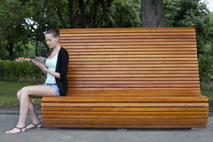 Young woman using a tablet computer on a park Stock Images