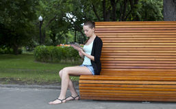 Young woman using a tablet computer on a park Stock Photos
