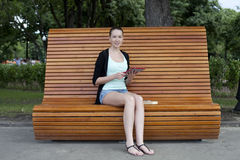 Young woman using a tablet computer on a park Royalty Free Stock Photography