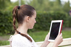 Young woman using a tablet computer on a park Stock Image