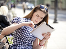 Young woman using a tablet computer on a park Royalty Free Stock Photos