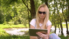 Young woman using tablet computer in the park, slow motion. Young woman using tablet computer in the park, slow motion stock video