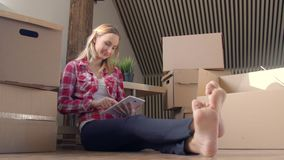 Young woman using tablet computer while sitting on floor at her new home. stock video