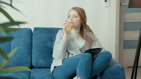 Young woman using tablet computer while sitting on sofa. Young caucasian woman using tablet computer while sitting on sofa at home stock video footage
