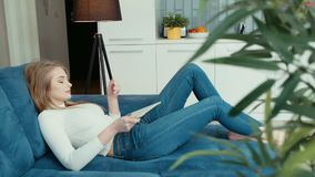 Young woman using tablet computer while sitting on sofa. Young caucasian woman using tablet computer while sitting on sofa at home stock video